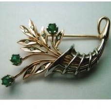 Брошь из комбинированного золота с бриллиантами и изумрудами..